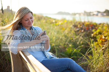 Young Woman Sitting on Bench at Beach, Texting on Cell Phone, Jupiter, Palm Beach County, Florida, USA Stock Photo - Premium Royalty-Free, Image code: 600-06701918
