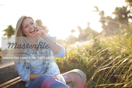 Young Woman Sitting on Bench at Beach, using Cell Phone, Jupiter, Palm Beach County, Florida, USA Stock Photo - Premium Royalty-Free, Image code: 600-06701920