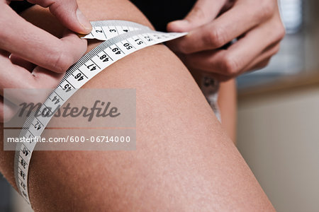 Close-up of Woman Measuring her Thigh with Tape Measure Stock Photo - Premium Royalty-Free, Image code: 600-06714000