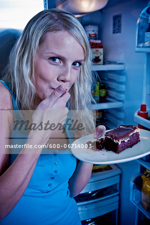 Young Woman Eating Cake by Open Refrigerator Stock Photo - Premium Royalty-Free, Image code: 600-06714003