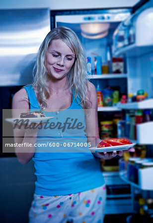 Young Woman Deciding between Cake or Veggies by Open Refrigerator Stock Photo - Premium Royalty-Free, Image code: 600-06714005