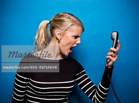 Young Woman Screaming at Telephone, Studio Shot Stock Photo - Premium Royalty-Free, Image code: 600-06714008