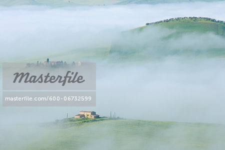 Typical Tuscany landscape with farm in morning with fog near Pienza. Pienza, Siena district, Tuscany, Toscana, Italy.