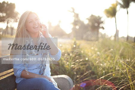 Young Woman Sitting on Bench at Beach using Cell Phone, Jupiter, Palm Beach County, Florida, USA Stock Photo - Premium Royalty-Free, Image code: 600-06732635