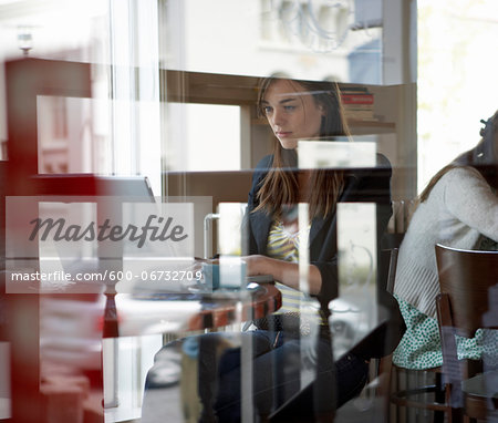 Young woman with laptop computer sitting in a cafe.  Seen through a glass window, Reykjavik, Iceland Stock Photo - Premium Royalty-Free, Image code: 600-06732709