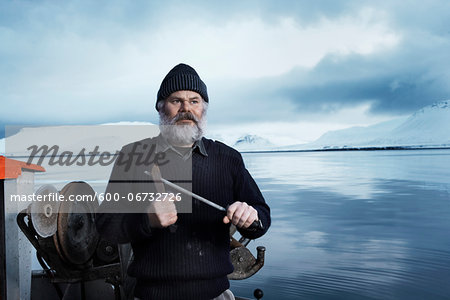 Fisherman with gray beard, standing on small boat, sharpening a knife on a winter day, Iceland. Stock Photo - Premium Royalty-Free, Image code: 600-06732726