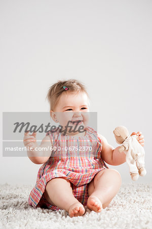 Portrait of Baby Girl Laughing and holding Teddy Bear, Studio Shot Stock Photo - Premium Royalty-Free, Image code: 600-06752370