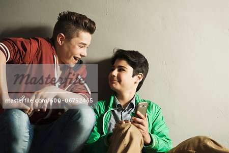 Teenagers looking at Cell Phone, Studio Shot Stock Photo - Premium Royalty-Free, Image code: 600-06752465