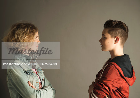 Teenage Boy and Girl Staring at Each Other with Arms Crossed, Studio Shot Stock Photo - Premium Royalty-Free, Image code: 600-06752488