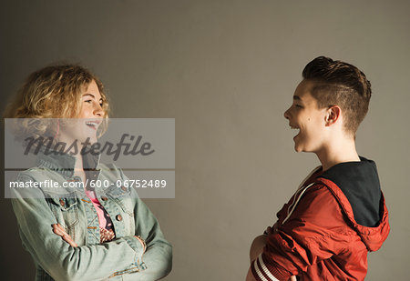 Teenage Boy and Girl looking at Each Other and Laughing, Studio Shot Stock Photo - Premium Royalty-Free, Image code: 600-06752489