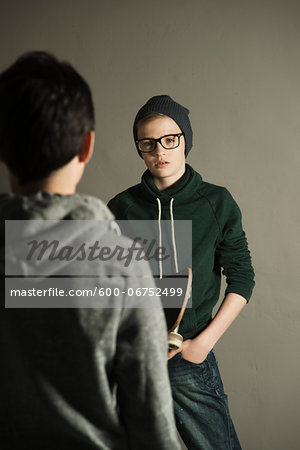 Boy with Skateboard talking to Teenage Boy, Studio Shot Stock Photo - Premium Royalty-Free, Image code: 600-06752499