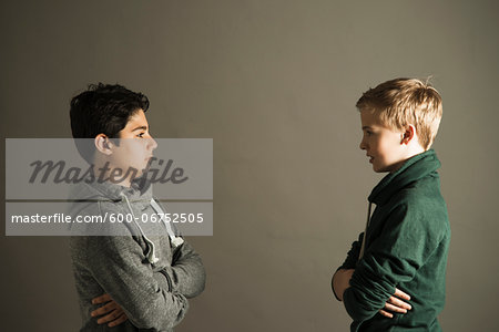 Teenage Boys with Arms Crossed looking at Each Other, Studio Shot Stock Photo - Premium Royalty-Free, Image code: 600-06752505