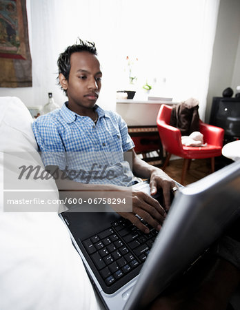 Young Man on Sofa using Laptop Stock Photo - Premium Royalty-Free, Image code: 600-06758294