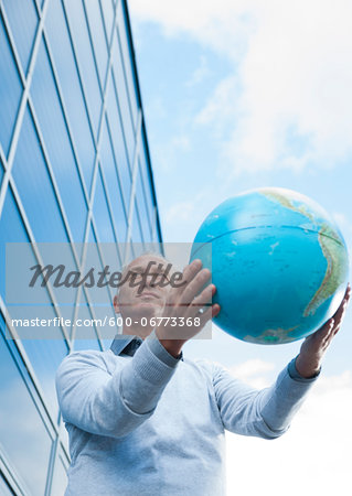 Businessman Holding Globe Outdoors, Mannheim, Baden-Wurttemberg, Germany Stock Photo - Premium Royalty-Free, Image code: 600-06773368