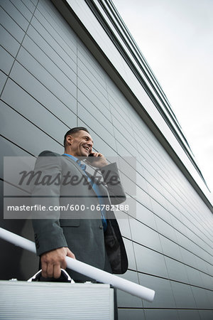 Businessman standing in front of wall of building using cell phone, Mannheim, Germany Stock Photo - Premium Royalty-Free, Image code: 600-06782188