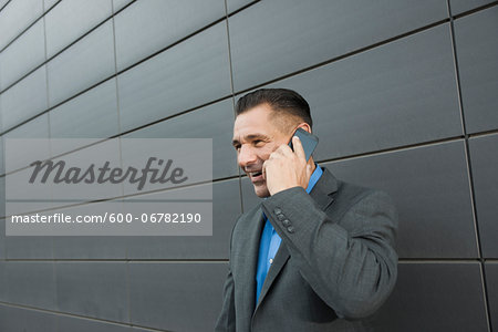 Close-up portrait of businessman standing in front of wall of building using cell phone, Mannheim, Germany Stock Photo - Premium Royalty-Free, Image code: 600-06782190