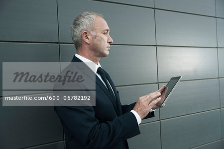 Mature businessman standing in front of wall, looking at tablet computer Stock Photo - Premium Royalty-Free, Image code: 600-06782192