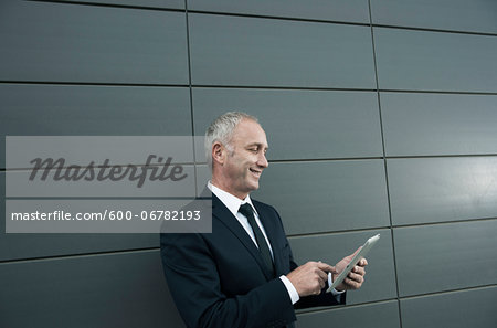 Mature businessman standing in front of wall, looking at tablet computer Stock Photo - Premium Royalty-Free, Image code: 600-06782193