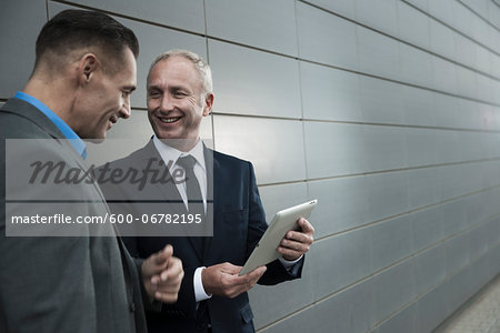 Mature businessmen standing in front of wall, talking and looking at tablet computer Stock Photo - Premium Royalty-Free, Image code: 600-06782195