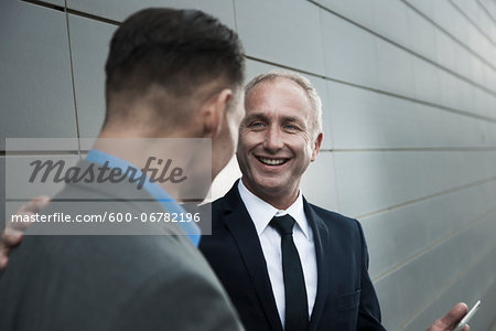 Mature businessmen standing in front of wall, talking Stock Photo - Premium Royalty-Free, Image code: 600-06782196