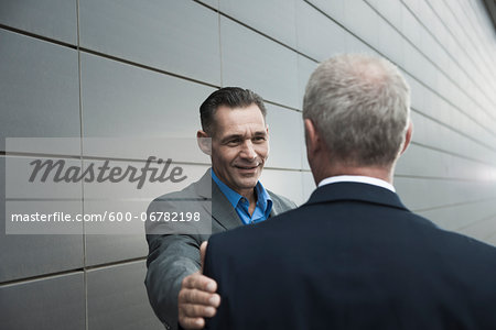 Mature businessmen standing in front of wall, talking Stock Photo - Premium Royalty-Free, Image code: 600-06782198