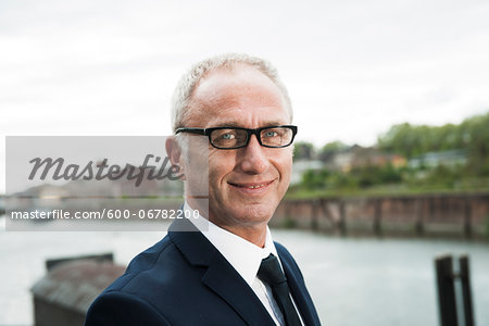 Portrait of mature businessman outdoors, wearing horn-rimmed eyeglasses, smiling at camera, Mannheim, Germany Stock Photo - Premium Royalty-Free, Image code: 600-06782200