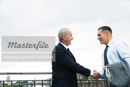 Mature businessmen standing by railing, shaking hands outdoors, Mannheim, Germany Stock Photo - Premium Royalty-Free, Image code: 600-06782202