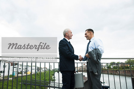 Mature businessmen standing by railing, shaking hands outdoors, Mannheim, Germany Stock Photo - Premium Royalty-Free, Image code: 600-06782203
