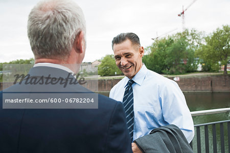 Mature businessmen standing by railing talking, Mannheim, Germany Stock Photo - Premium Royalty-Free, Image code: 600-06782204