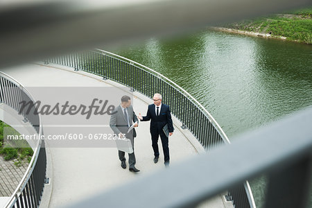 Mature businessmen on walkway talking, Mannheim, Germany Stock Photo - Premium Royalty-Free, Image code: 600-06782213