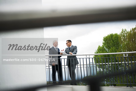 Mature businessmen standing on bridge talking, Mannheim, Germany Stock Photo - Premium Royalty-Free, Image code: 600-06782215