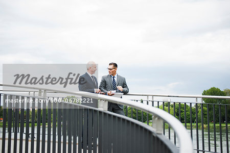 Mature businessmen standing on bridge talking, Mannheim, Germany Stock Photo - Premium Royalty-Free, Image code: 600-06782221
