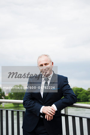 Portrait of mature businessman standing on bridge, smiling at camera and leaning on railing, Mannheim, Germany Stock Photo - Premium Royalty-Free, Image code: 600-06782224