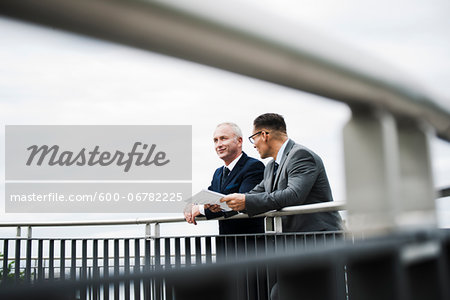 Mature businessmen standing on bridge talking, Mannheim, Germany Stock Photo - Premium Royalty-Free, Image code: 600-06782225
