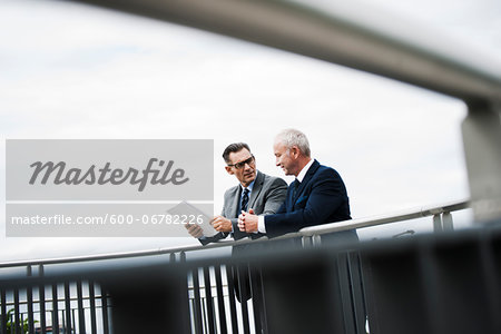 Mature businessmen standing on bridge talking, Mannheim, Germany Stock Photo - Premium Royalty-Free, Image code: 600-06782226
