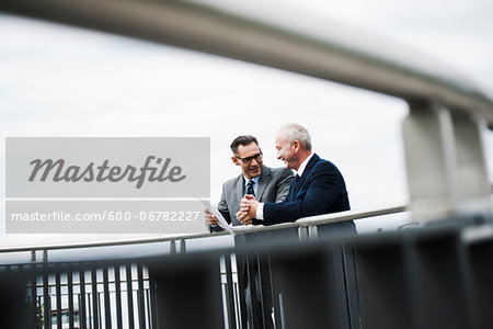 Mature businessmen standing on bridge talking, Mannheim, Germany Stock Photo - Premium Royalty-Free, Image code: 600-06782227