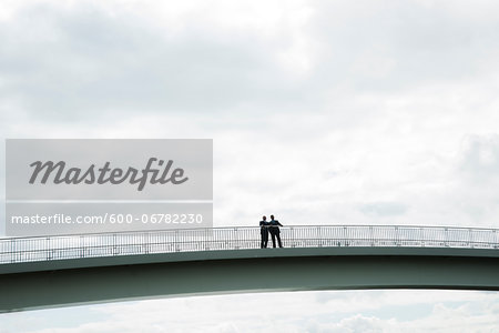 Silhouette of mature businessmen standing on bridge talking, Mannheim, Germany Stock Photo - Premium Royalty-Free, Image code: 600-06782230