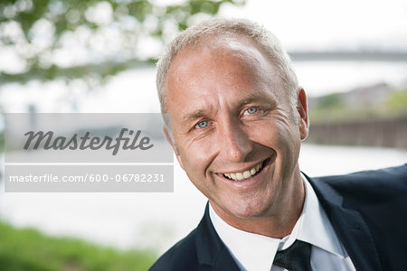 Close-up portrait of mature businessman smiling at camera Stock Photo - Premium Royalty-Free, Image code: 600-06782231