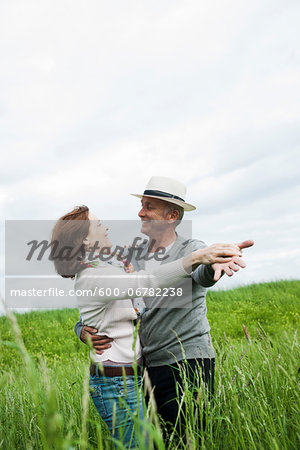 Mature couple dancing in field of grass, Germany Stock Photo - Premium Royalty-Free, Image code: 600-06782238