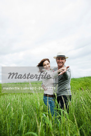 Mature couple dancing in field of grass, smiling at camera, Germany Stock Photo - Premium Royalty-Free, Image code: 600-06782239
