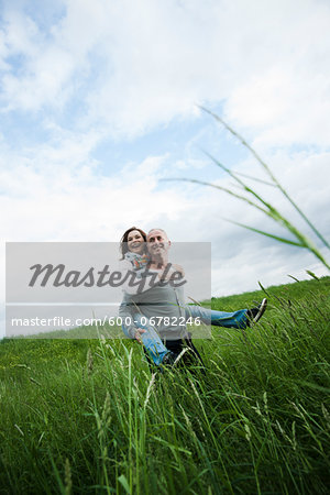 Mature couple in field of grass, man giving piggyback ride to woman, Germany Stock Photo - Premium Royalty-Free, Image code: 600-06782246