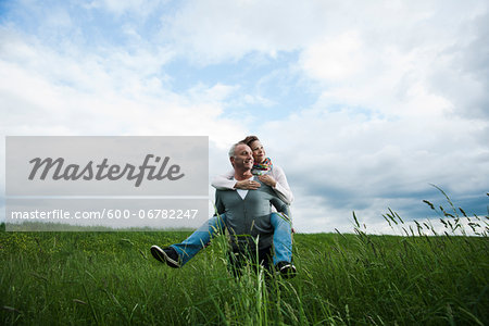 Mature couple in field of grass, man giving piggyback ride to woman, Germany Stock Photo - Premium Royalty-Free, Image code: 600-06782247