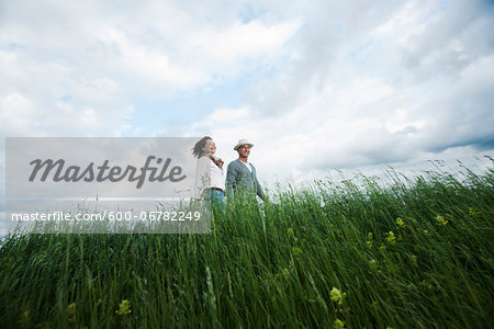 Mature couple walking in field of grass, Germany Stock Photo - Premium Royalty-Free, Image code: 600-06782249