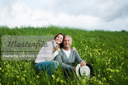 Portrait of mature couple sitting in field of grass, embracing, Germany