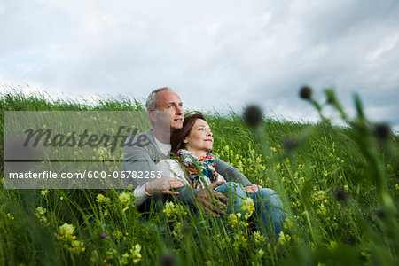 Mature couple sitting in field of grass, embracing, Germany Stock Photo - Premium Royalty-Free, Image code: 600-06782253