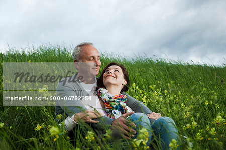 Mature couple sitting in field of grass, embracing, Germany Stock Photo - Premium Royalty-Free, Image code: 600-06782254