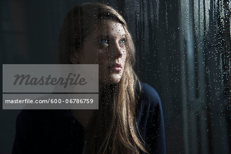 Portrait of young woman behind window, wet with raindrops, looking up Stock Photo - Premium Royalty-Free, Image code: 600-06786759
