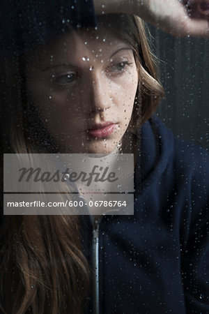 Portrait of young woman behind window, wet with raindrops, wearing hoodie Stock Photo - Premium Royalty-Free, Image code: 600-06786764