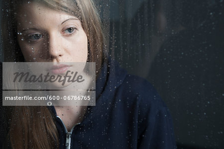 Portrait of young woman behind window, wet with raindrops, wearing hoodie Stock Photo - Premium Royalty-Free, Image code: 600-06786765