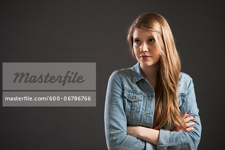 Portrait of young woman with long, blond hair, studio shot on grey background Stock Photo - Premium Royalty-Free, Image code: 600-06786766